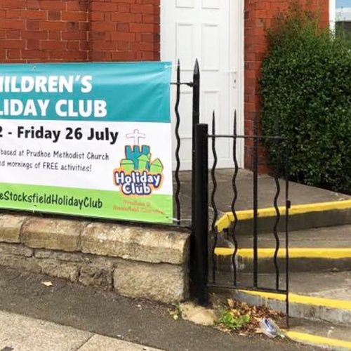 Reusable banner for a holiday club hanging from a fence