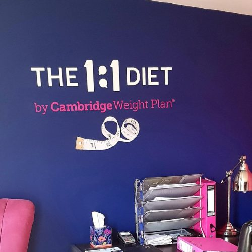 The 1:1 Diet Logo Decal applied onto a purple wall in an office